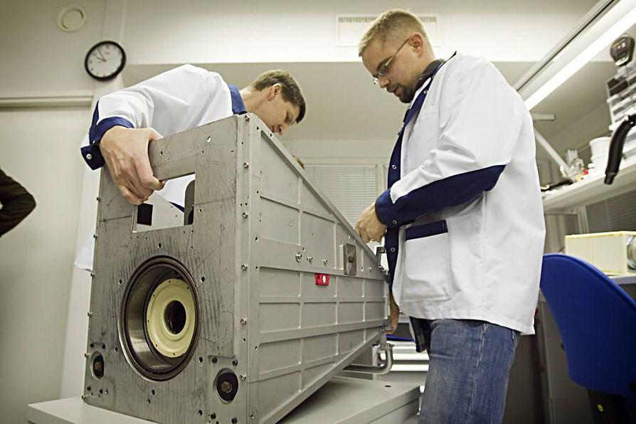 Elektroniikka-asentajat Petri Räisänen (oik.) ja Esa Sirviö tarkastelevat kaukokartoituksessa käytettävää hyperspektraalikameraa.