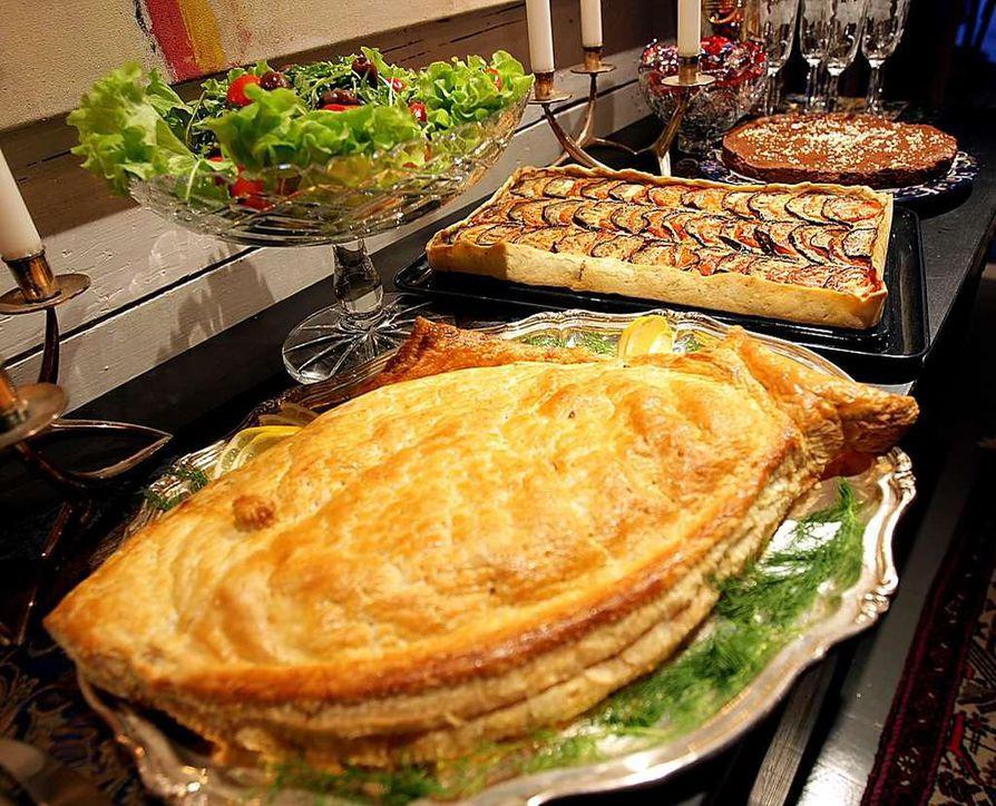 Vuodenvaihteen kekkereissä noutopöytä on helppo vaihtoehto. Vanhan ajan lohipiirakan voi muotoilla myös kalan muotoon. Kasvispiirakka ja salaatti täydentävät pöydän.