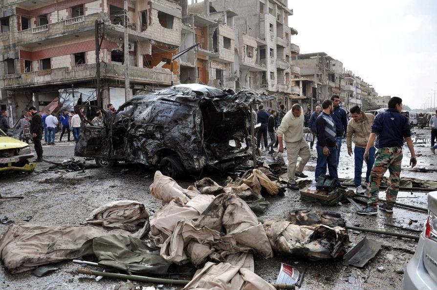 Kuva viikon takaa Homsin kaupungista, jossa syyrialaiset poliisit ja siviilit tutkivat kaksoispommi-iskun jälkiä.
