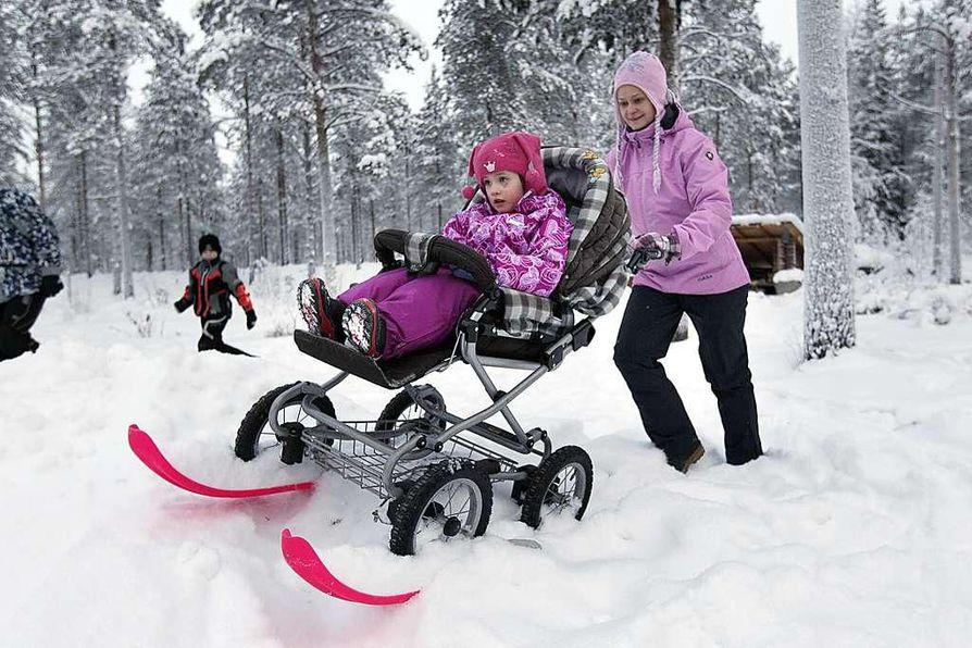Aitto-ojan perheen lasten, Tytin ja Hermannin, mielestä rattaissa on mukavampi kulkea kuin pulkassa. Idea vaunusuksiin syntyi talvisella kävelyretkellä. Kuvassa vaunuja työntää Tuija Aitto-oja.