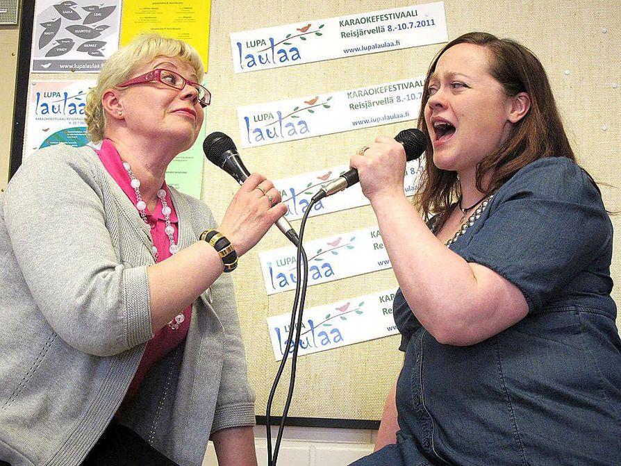 Projektisihteeri Tiina Kesänen (vas.) ja tapahtumapäällikkö Marita Pasanen virittelevät tässä tunnelmia Lupa laulaa -karaoketapahtumaan, joka järjestetään heinäkuussa Reisjärvellä.