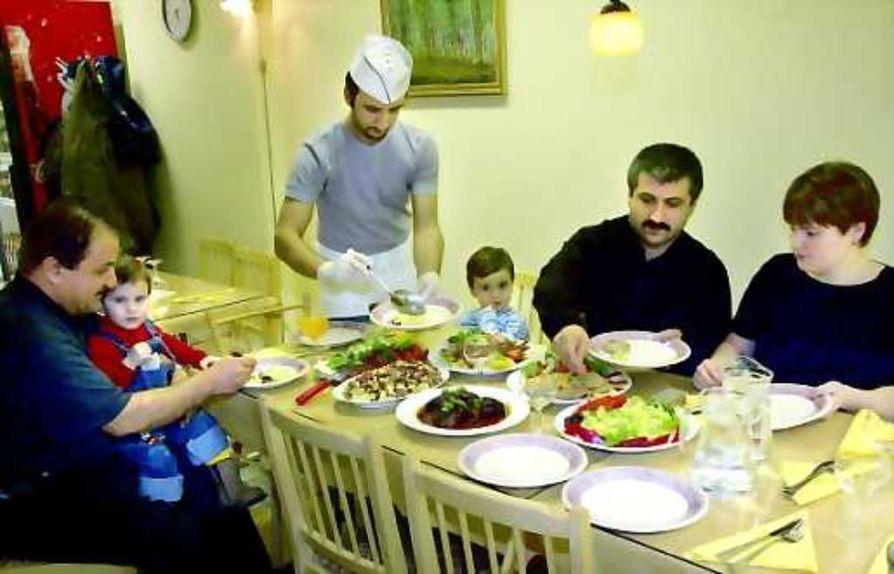 Assyrialaisella aterialla. Yhteinen ateria on tärkeä assyrialaisessa kulttuurissa. Kokinhattuinen Evel on valmistanut perheelleen juhla-aterian, jossa valittavana on sekä lihaa että kalaa. Isoisä Pauluksen sylissä Ninos. Isoveli Atran aterioi isänsä Awonerin  ja äitinsä Marin vieressä.