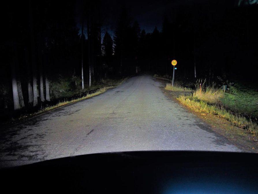 Tässä kuvassa palavat kaukovalot, vaikka pimeä metsä imee osan niidenkin tehosta. Risteykset, liikennemerkit ja muut kulkijat tulevat kuitenkin näkyviin nopeammin ja kuljettajalle jää enemmän reagointiaikaa.