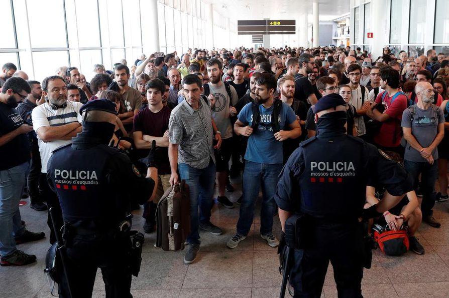 Kaksi Katalonian alueellista poliisia valvoi sisäänpääsyä Barcelonan lentokentän terminaaliin. Valtava joukko ihmisiä pyrki lentokentälle osoittamaan mieltään maanantaina.