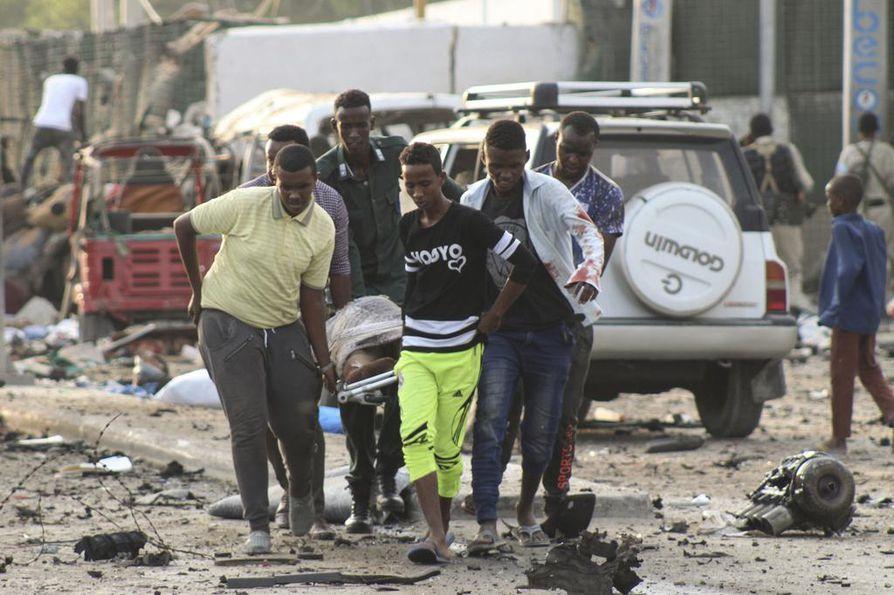 Ihmiset auttoivat Mogadishun perjantaisessa itsemurhaiskussa loukkaantunutta. Ainakin 22 on kuollut.