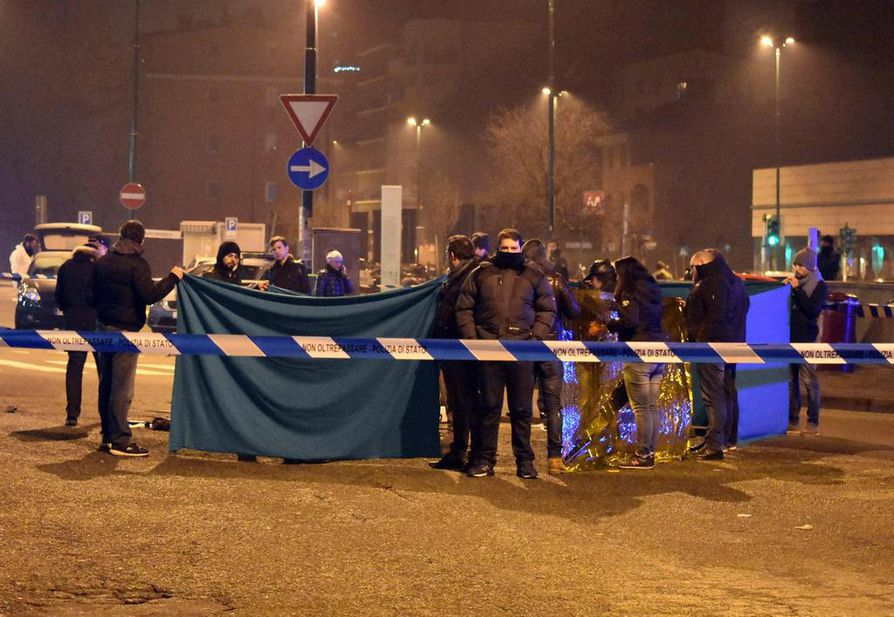 epa05686425 Italian police use blankets to prevent a direct view of a dead body at the sealed off scene of a shootout between police and a man in Milan's Sesto San Giovanni neighborhood, early 23 December 2016. Italy's Interior Minister Marco Minitti meanwhile has confirmed that the identity of the individual shot dead after a gunfight with Italian police this morning near Milan is Anis Amri, the 24 year old Tunisian suspected of the 19 December Berlin Christmas Market terrorist truck attack, that left at least 12 people dead and around 50 others injured.  EPA/DANIELE BENNATI