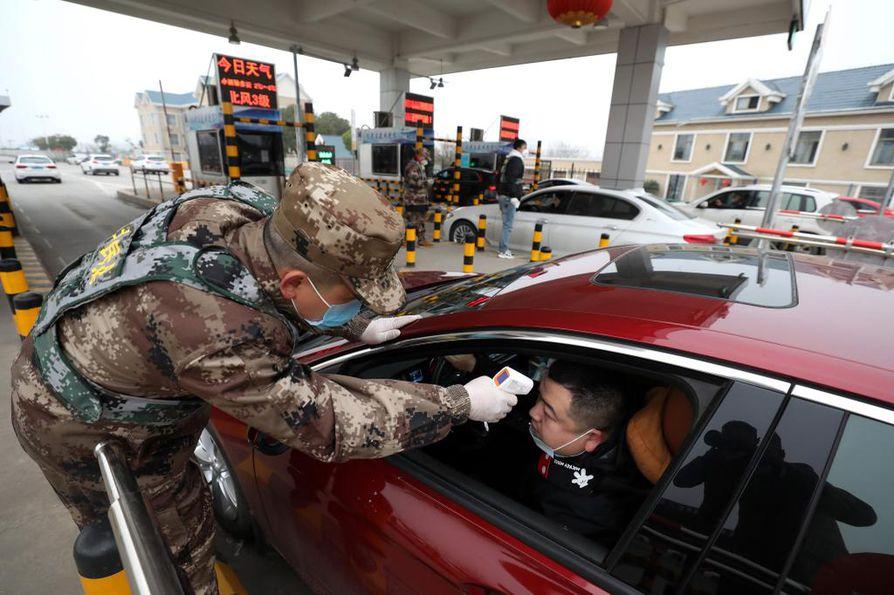 Miliisi mittasi kuskin ruumiin lämmön tietullilla Wuhanissa. Kiinassa jo 18 ihmistä tappaneen viruksen uskotaan lähteneen liikkeelle kaupungista.