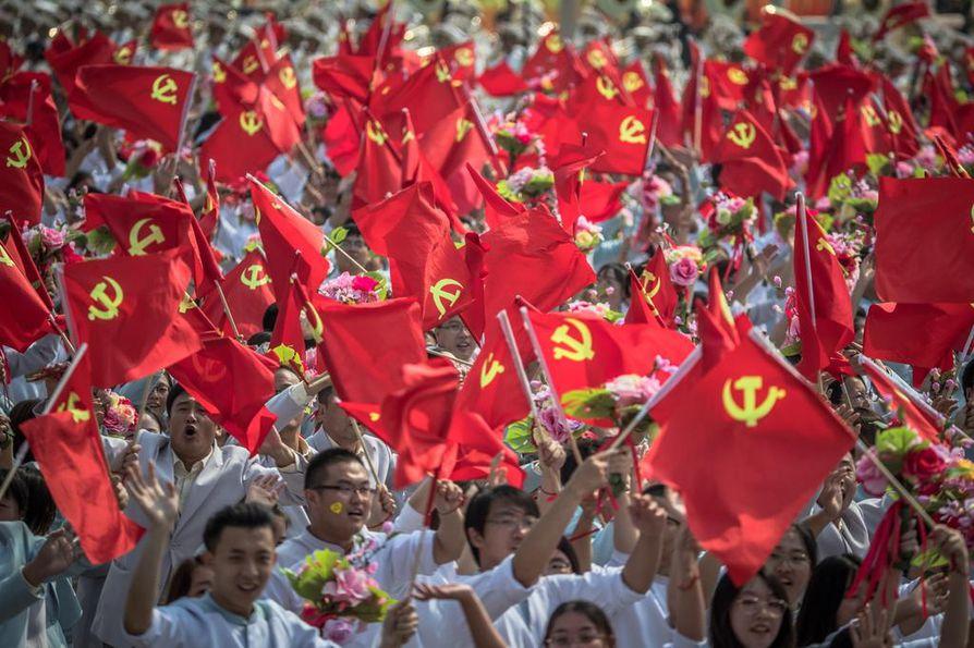 Osallistujat heiluttivat Kiinan kommunistisen puolueen lippuja marssiessaan Tiananmenin aukion yli sotilasparaatin yhteydessä Pekingissä 1. lokakuuta. Kuvituskuva.