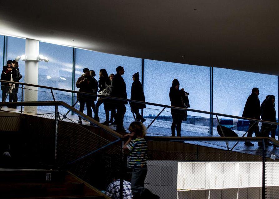 Keskustakirjasto Oodin ylimmän kerroksen päätyrakenteissa lasi leikkii vaalean puun ja valo vierailijoiden siluettien kanssa.