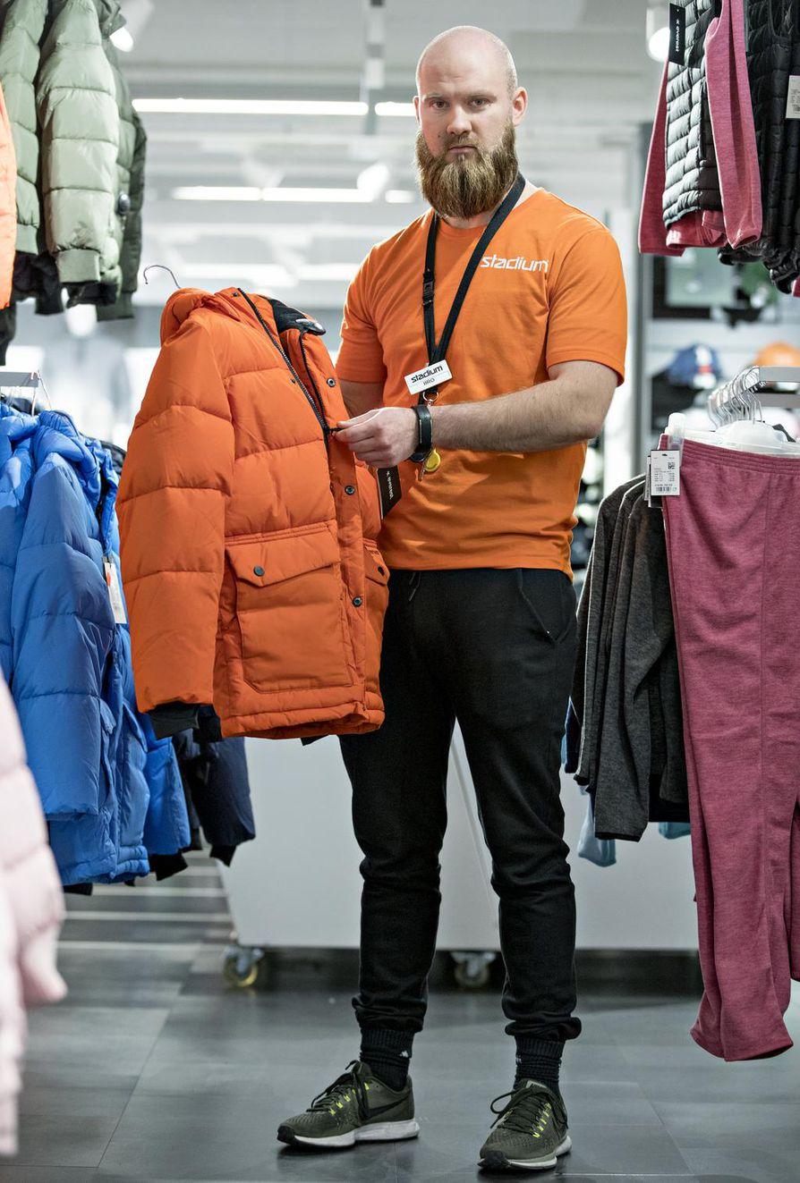 Stadiumin myyjä Iiro Molander esittelee talvitakkia. Edullisempia pikkuvikaisia reklamoituja vaatteita ei liikkeessä juuri korjauteta, vaan ne lahjoitetaan hyväntekeväisyyteen.