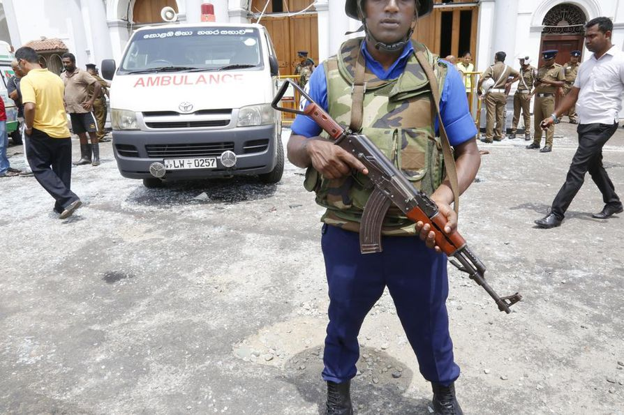 Vartija seisoo räjähdysten jälkeen vartiossa St. Anthonyn kirkon edessä Sri Lankan Colombossa.