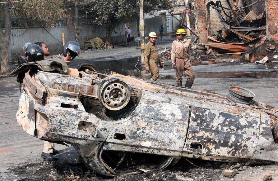 Pelastajat kävelivät palaneiden autojen seassa Intian pääkaupungissa Delhissä keskiviikkona.