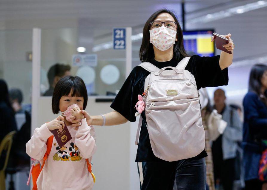 Kiinan Kantonista matkustaneet nainen ja lapsi suojautuivat kasvomaskeilla Philippiineillä Manilan lentokentällä keskiviikkona.