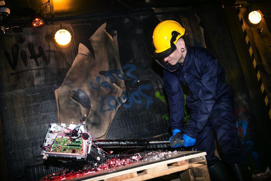 Ville Pukkinen mäjäyttää vanhan tulostimen tohjoksi Seinäjoen Vihahuoneella. Vihahuone on elämyskonsepti, josta etenkin polttariporukat ovat innostuneet.