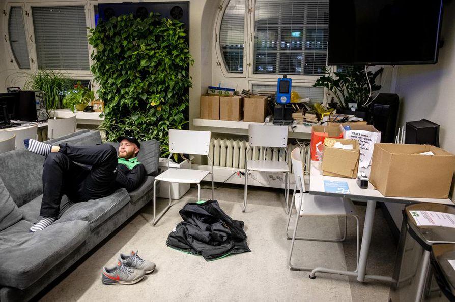 Lähiliikennekonduktööri Teemu Rautanen loikoilee sohvalla kännykkäänsä selaillen. Asemarakennuksen länsisiivessä on junahenkilökunnan taukotilat, ja sinne on järjestetty myös nukkumismahdollisuus esimerkiksi kaukojunien henkilökunnalle.