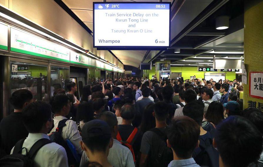 Matkustajat jonottavat ruuhkautuneella rautatieasemalla Hongkongissa.