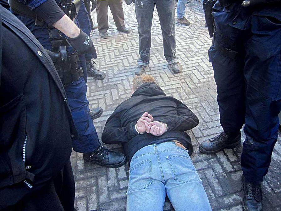 Poliisi joutui käyttämään muun muassa etälamautinta kiivastuneisiin kansanedustajaehdokkaiden kimppuun hyökänneisiin miehiin. Kuvassa yksi käsirautoihin laitetuista miehistä.