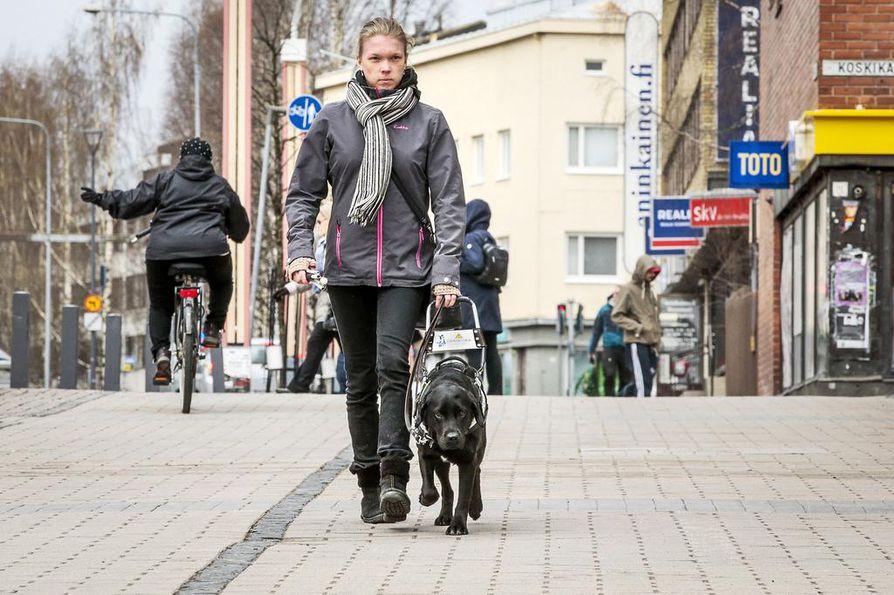 Raisa Kuusela kulkee opaskoiransa kanssa tuttuja reittejä rivakkaa vauhtia. Koiraansa hän ei näe, vaan hän pitää opaskoiran valjaskahvasta kiinni ja tunnistaa siten koiran liikkeistä erilaisia asioita.