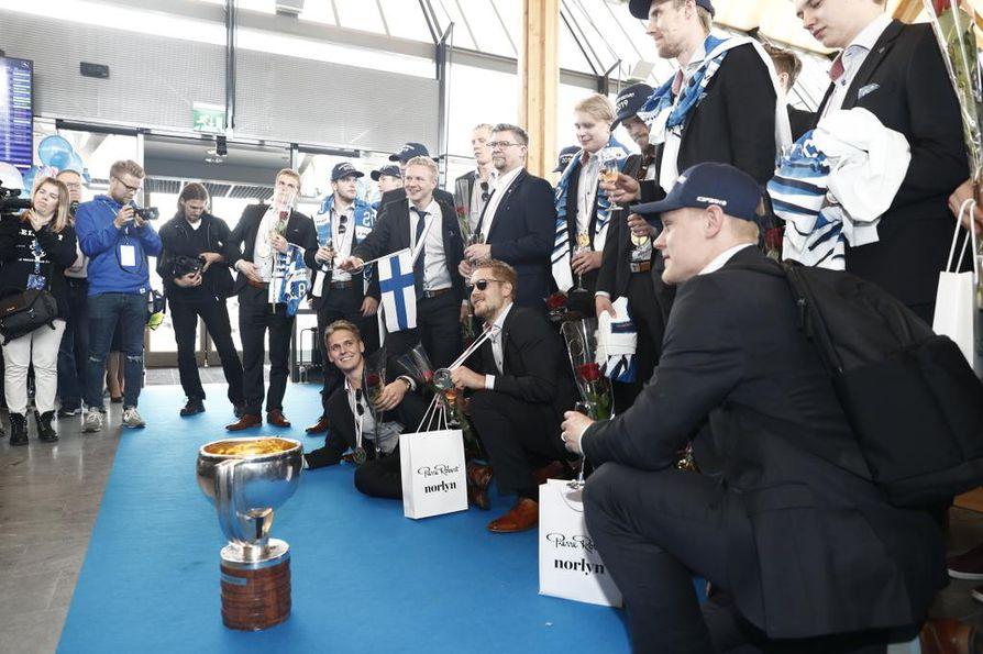 Kultajoukkue poseerasi medialle iloisina Helsinki-Vantaan terminaalissa maanantai-iltapäivällä.