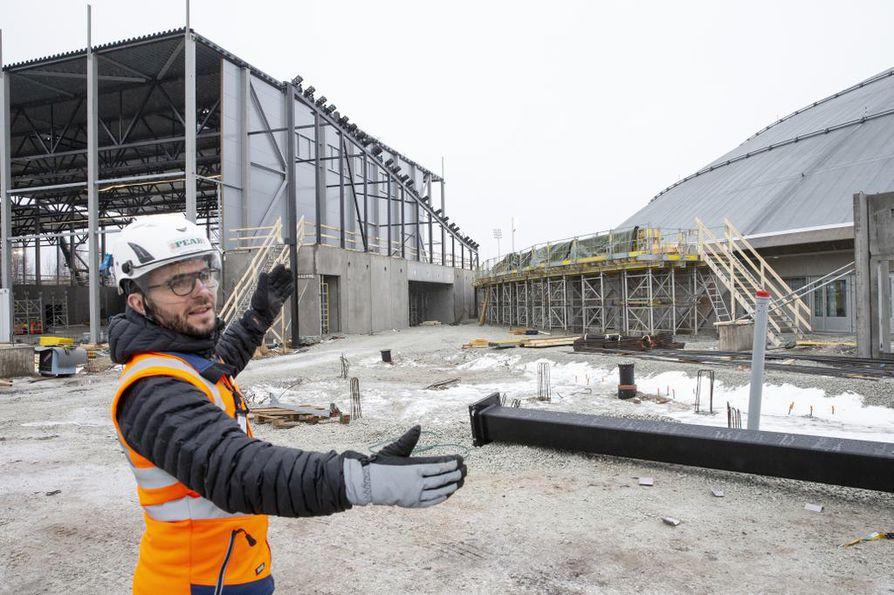 PEAB:n työpäällikkö Anssi Wallenius esittelee rakennusten liitoskohtaa, jossa sijaitsee tulevaisuudessa aula ja ravintola.