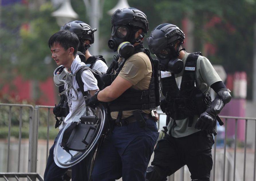 Mellakkapoliisi pidätti mielenosoittajan yhteenoton aikana yliopiston ulkopuolella.