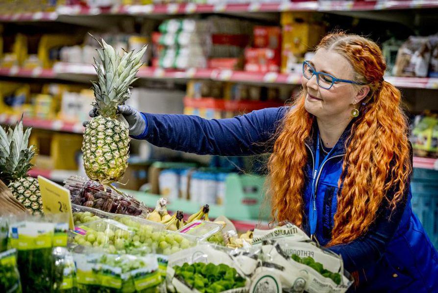Marjut Heinonen tarttuu ananaksesta hedelmän ja lehtien taitekohdasta kiinni, siirtää sen hyllyssä oikeaan kohtaan ja toteaa, että kahta samanlaista työpäivää ei ole.