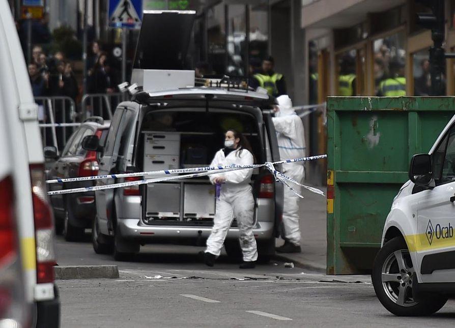 Poliisin tutkijat tutkivat iskupaikkaa Tukholman keskustassa lauantaina päivällä.
