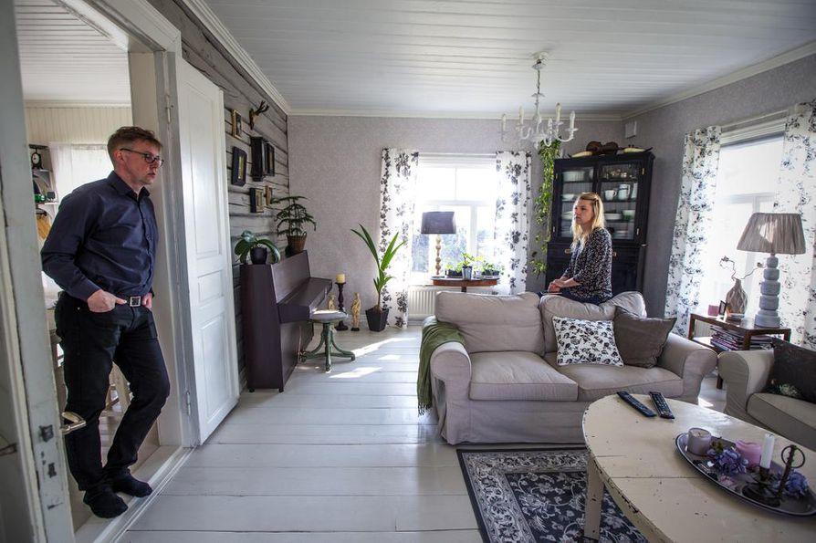 Mika ja Virpi Billing remontoivat taloaan noin neljä vuotta. Olohuoneen valtavan leveät lankut löytyivät puuvajasta. Ne käytiin sahauttamassa saman paksuisiksi, mutta paikalleen sovittelu oli iso urakka. Hirsiseinä on maalattu harmaalla kalkkimaalilla. Mustan kaapin alaosa on ollut perheessä pitkään. Nyt Virpin isä nikkaroi siihen yläosan, jonka ovina ovat vanhat ikkunat – ja arvokkaannäköinen astiakaappi oli valmis. Sohvapöytä on vanha patinoitunut ruokapöytä, jonka jalat sahattiin lyhyiksi.