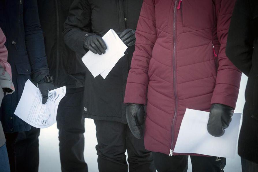 Ekaluokkalaisten vanhemmat pitävät käsissään päätöksisä, joissa oppilaat on hyväksytty Ritaharjun koulun oppilaiksi.
