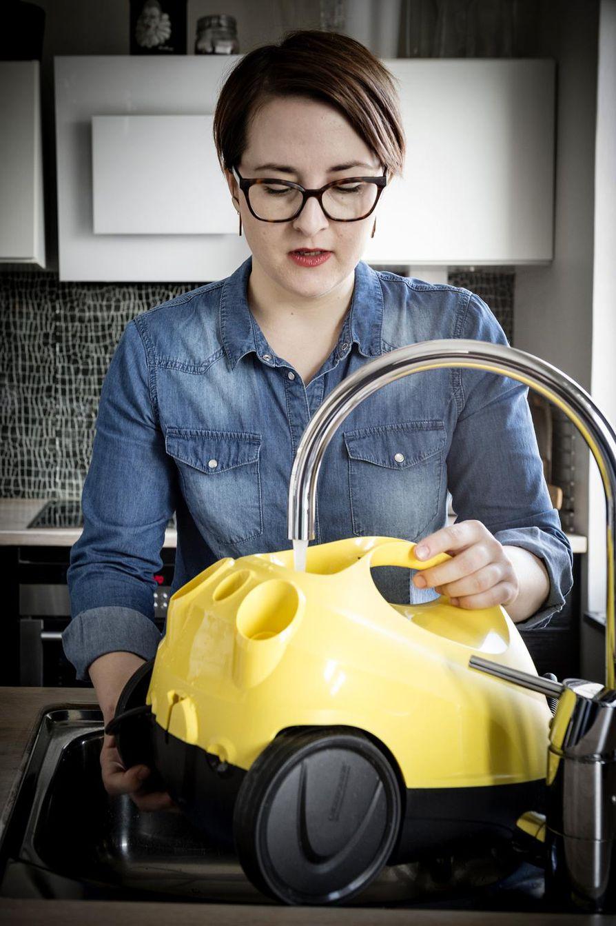 Höyrypuhdistimen vesisäiliö täytetään yksinkertaisesti hanan alla, Marjut Ollila näyttää.
