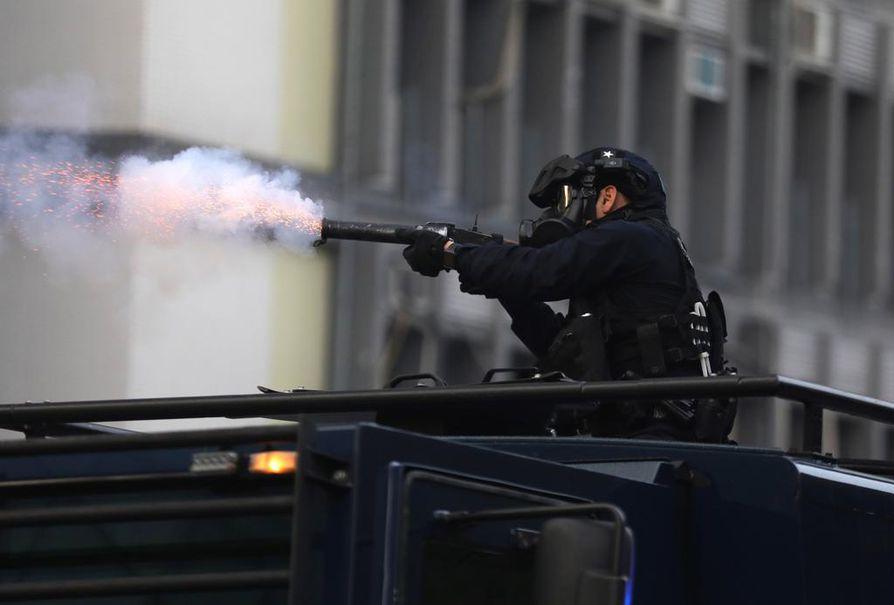 Mellakkapoliisin viranomainen laukaisee kyynelkaasua kohti protestoijia.