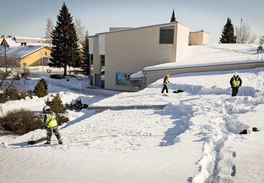 Muhoksen Koivu ja Tähti -kulttuurikeskuksen katolta pudotettiin lumia. Lunta pudottamassa (vas.) Elias Holmi, Katri Holmi ja Jere Leskelä.
