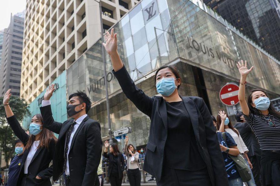 Toimistotyöntekijät liittyivät väkijoukkoon ruokatuntinsa aikana Hongkongissa torstaina.