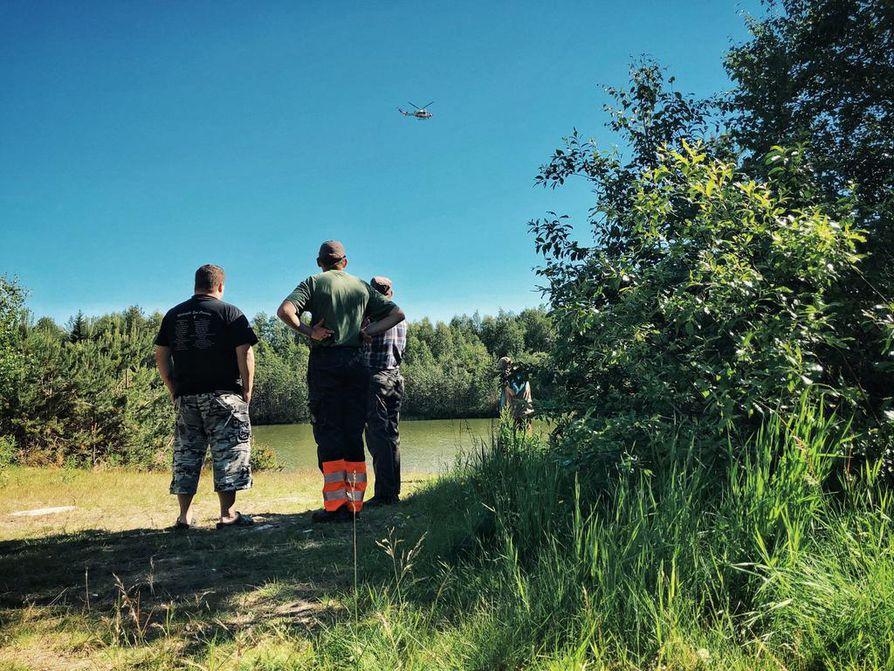 Rajavartioston helikopteri kiertää paikkaa, mihin lentokone putosi.  Paikalla on paikallisia asukkaita katsomassa paikkaa, josta savu nousi. Koneen utoamispaikka on vesistön toisella puolella.
