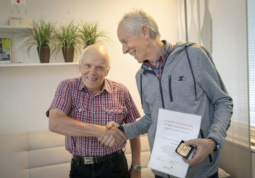 Pelastettu ja palkittu Lauri Malm (oik.) SPR:n toimistolla torstaina, kun Malmille myönnettiin ensiavun huomionosoitus.
