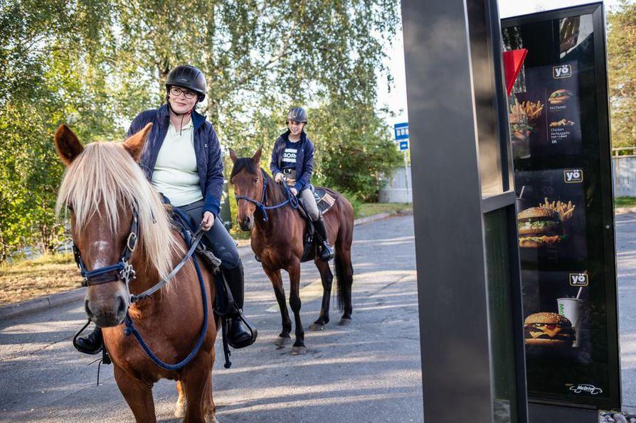 Mari Petäjäjärvi (vas.) ja Siiri Malinen ratsuineen keräsivät katseita Rovaniemen keskustan McDonaldsin autokaistalla perjantaina.