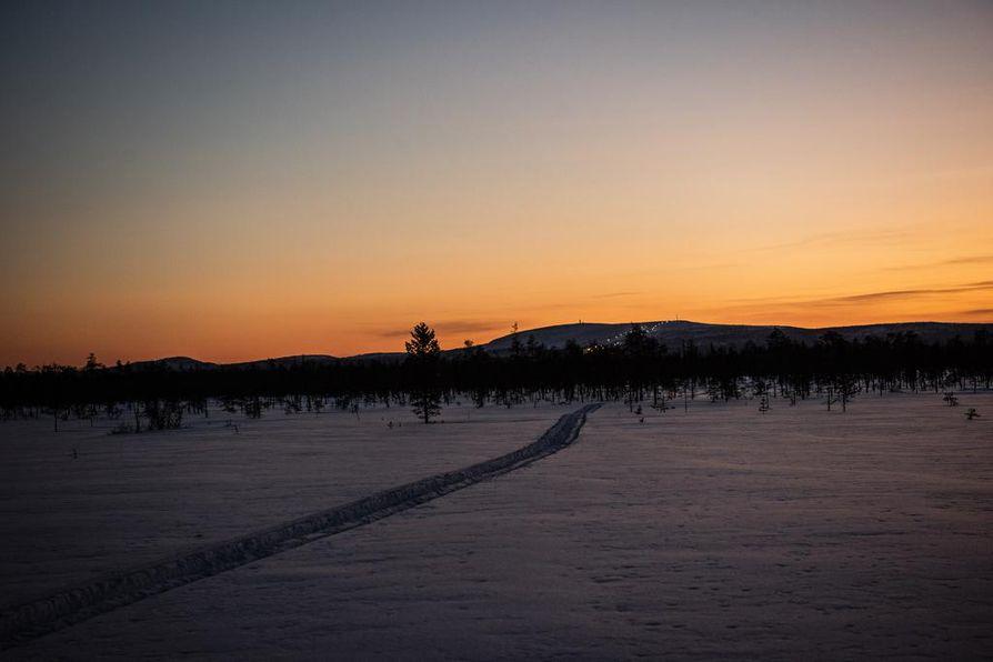 Paluumatkalla tulee pimeä. Silloin kelkanjälki helpottaa hiihtäjää. Etelässä näkyy Luosto ja sen laskettelurinteiden valot.