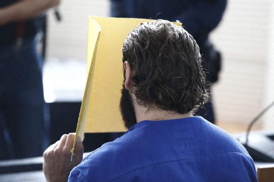 Nuorempi Porvoon poliisiammuskeluista epäilty mies peitti kasvonsa vangitsemisoikeudenkäynnin alussa.