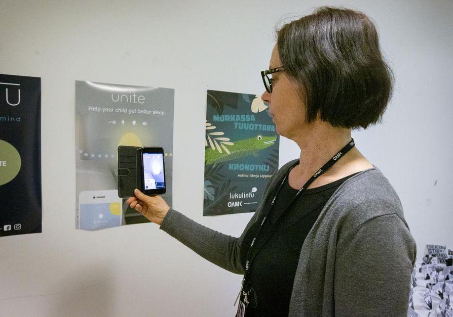 Oulun ammattikorkeakoulun viestinnän lehtori Karoliina Niemelä näyttää julisteita, jotka  toimivat lisätyn todellisuuden sisältöjen kohdistuspisteinä. Julisteiden suunnittelussa joutuu miettimään, mitä lisäarvoa lisätty todellisuus voi antaa. Kuvan julisteet ovat Oamkin opiskelijoiden töitä.