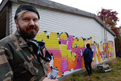 Hämmästyitkö rivitalon päätyseinän muraalia Oulaisissa? Hautakivitaiteilija Tomi Rajala kertoo, miten hänestä tuli graffititaiteen opettaja -katso video