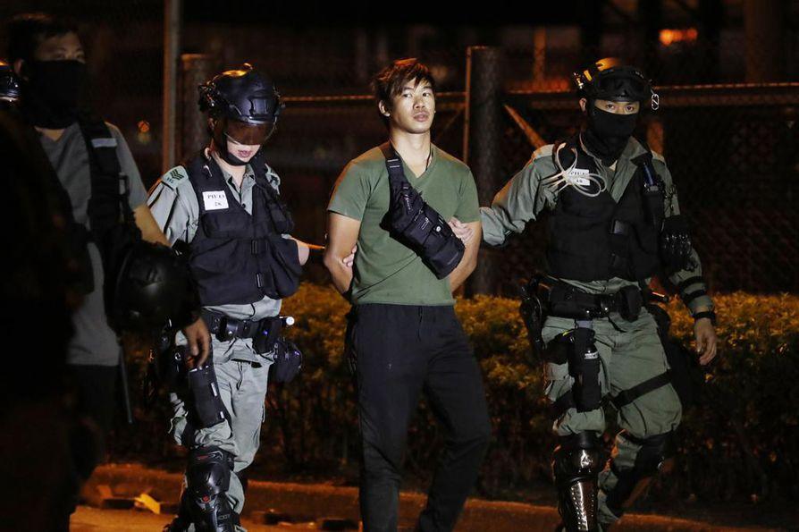 Poliisit taluttivat Hongkongin protesteissa pidättämäänsä miestä tiistaina.