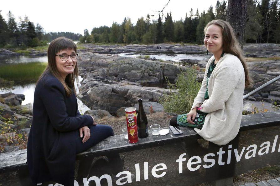 Sari Holappa ja Maija Kallio levähtivät sillan kaiteella. Holappa on käynyt festivaalilla kuudesti, ja usein hän on myös viettänyt aikaa kosken kivillä istuen.