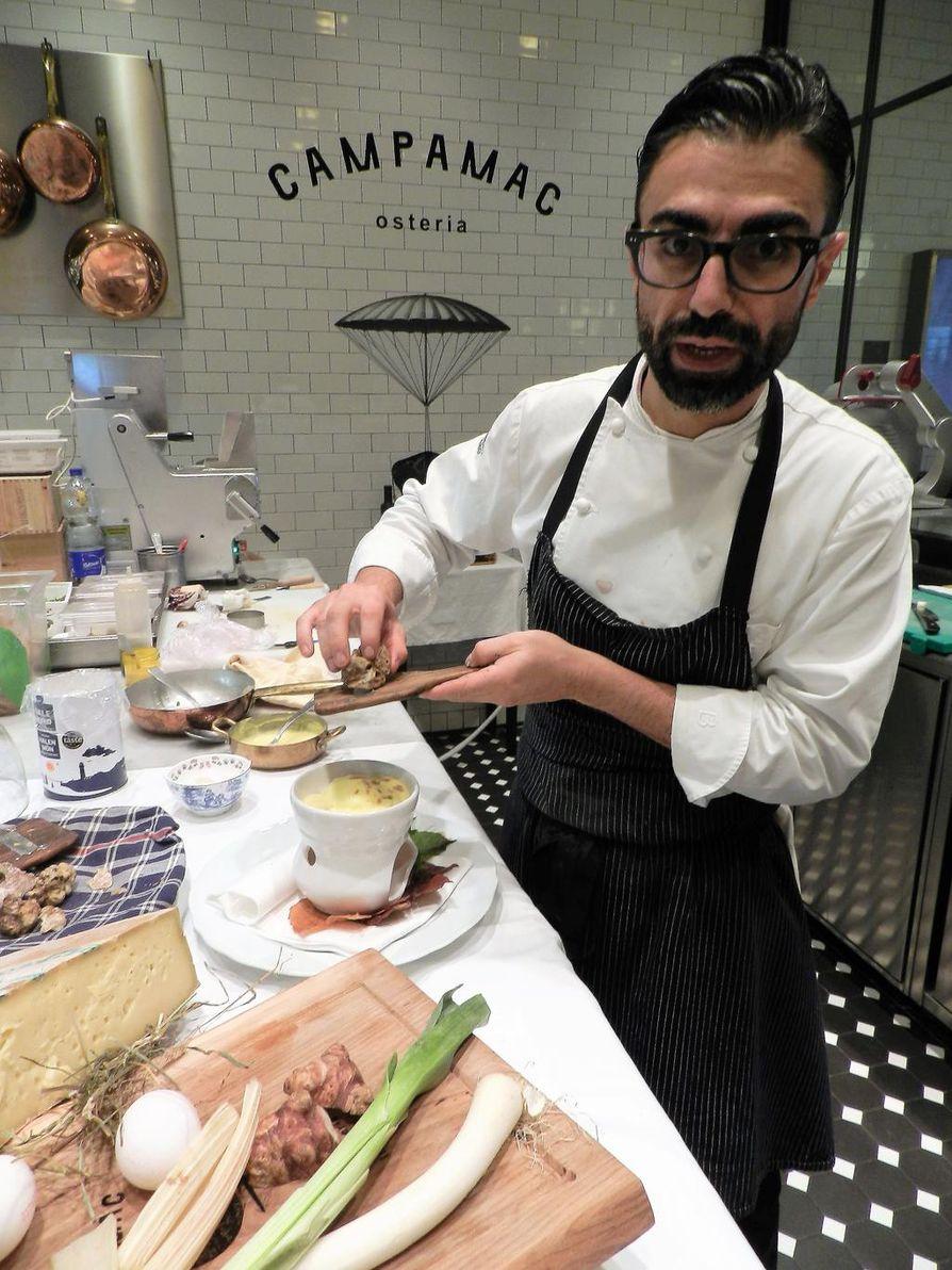 Keittiömestari Alessandro Capalbo höylää valkotryffeliä juuston ja munan päälle Campamac-osteriassa.