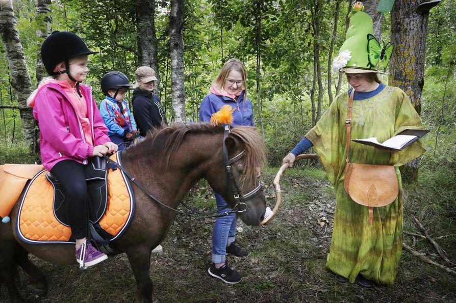 Tiia-Liisa Saarinen (oik.) kertoi tarinan Takun taikaliemestä. Yksi kommellus sattui, kun Takku erehtyi kaatamaan keskeneräistä sekoitusta  suoraan pajunoksille.