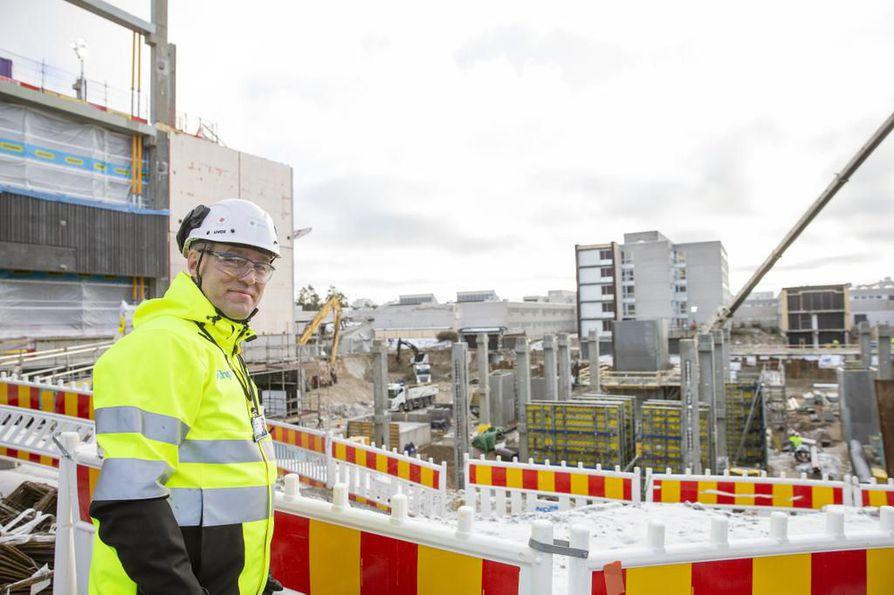 Ohjelmajohtaja Kari-Pekka Tampio seisoo valmisteluvaiheessa olevan B-rakennuksen edessä. Vasemmalla näkyvän ensimmäisen vaiheen A-rakennus on noussut jo neljänteen kerrokseen.