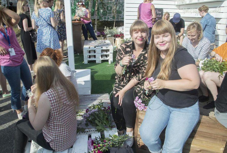 Vielä iltapäivällä keli oli hieno. Laura Eskola ja Eeva Kylén punoivat itselleen kukkaseppeleet.