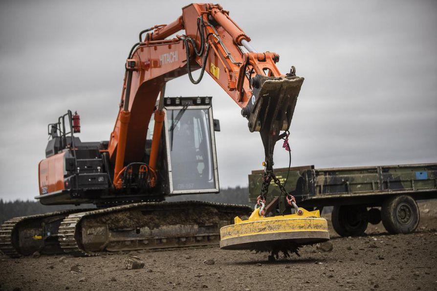 Kaivinkoneeseen kiinnitetty suuri magneetti siivoaa räjäytysalueelle levinneet metallinsirpaleet.