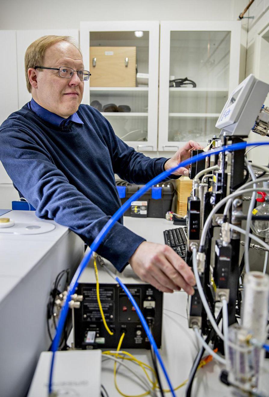 Dosentti Mika Huuhtanen säätää infrapunaspektrometrin kaasunsyöttöjärjestelmää.