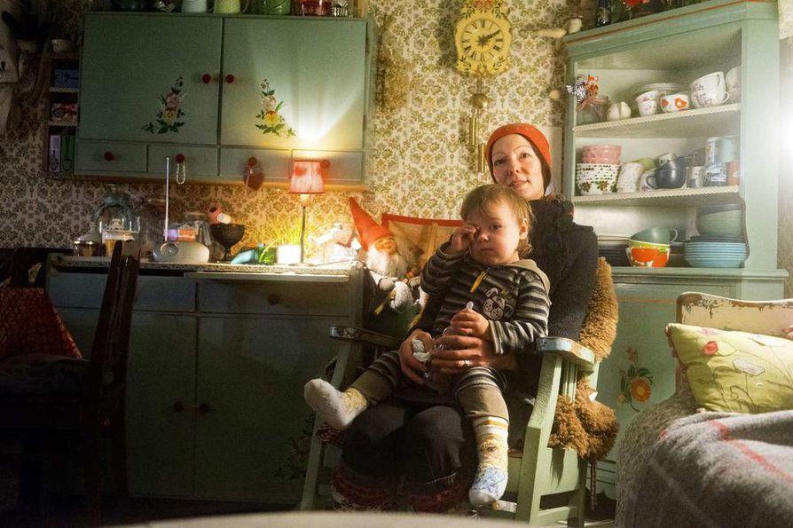 Emäntä Katja Jomppanen lempipaikassaan tuvassa. Elle-Karenilla on päiväunien aika.