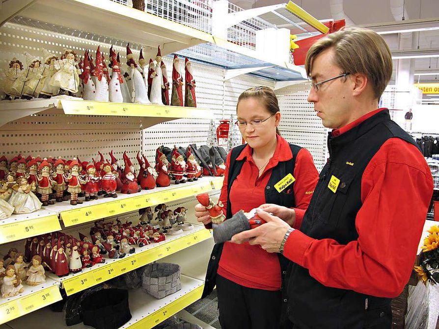 Halpa-Hallin Ylivieskan liikkeessä talousosaston myyjänä työskentelevä Marja-Liisa Niemi ja myymäläpäällikkö Janne Kurikkala asettelevat ensimmäisiä joulutavaroita  hyllylle. Vaikka joulukoristeet ovat jo myynnissä, joululauluja liikkeessä soitetaan vasta paria viikkoa ennen joulua.